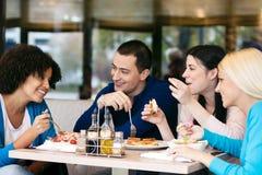 Gladlynta vänner som pratar medan lunch arkivbilder