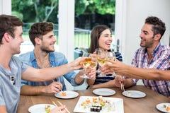 Gladlynta vänner som rostar vin, medan ha sushi Royaltyfri Foto