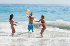 Gladlynta vänner som spelar med en beachball i havet Royaltyfri Foto