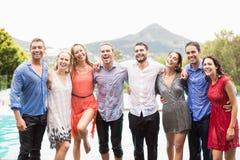 Gladlynta vänner som står vid simbassängen royaltyfri foto