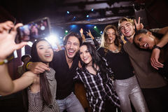Gladlynta vänner som tar selfie, medan tycka om på nattklubben Arkivbilder