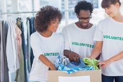 Gladlynta volontärer som ut tar kläder från en donationask Fotografering för Bildbyråer