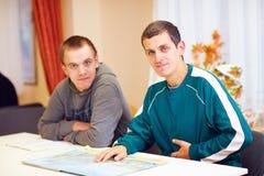 Gladlynta vuxna män med handikappsammanträde på skrivbordet i rehabiliteringmitt Royaltyfria Foton