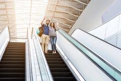 Gladlynta vuxna vänner står på rulltrappa arkivfoton