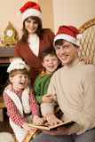 Gladness. Family gathered together by the fireplace before Christmas and reading a book Royalty Free Stock Images