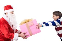 Gladness. Photo of joyful kid taking big present from Santa�s hands over white background royalty free stock photography