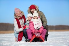 Gladness. Happy kids sitting on sledge with their parents near by royalty free stock image