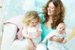 Gladness. Happy mother giving her children a hug, her daughter holding a gift-box royalty free stock image