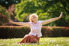 Gladness. Meditation. Mature Pleased Woman Relaxing with Outspread Arms. Happy Old Woman Relaxing with Outspread Arms in the Park stock photos