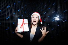 Gladness. Portrait of joyful businesswoman in Santa cap holding Crhistmas gift in nightclub royalty free stock photo
