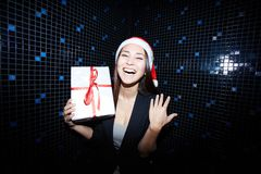Gladness. Portrait of joyful businesswoman in Santa cap holding Crhistmas gift in nightclub stock image