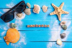 Gladness word with summer settings concept. Gladness word On Beach Accessories With Few Marine Items On Blue Wooden Plank , Summer concept royalty free stock photo