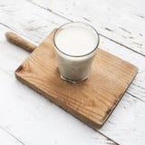 Glads mleko na nieociosanym białym drewnianym stole Zdrowy śniadanie, zdjęcia royalty free