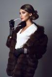 Glam модельное нося пальто ювелирных изделий и соболя с солнечными очками в ее руке Стоковые Изображения RF