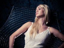 Glam girl. Studio portrait of a blonde model relaxing in a chair Royalty Free Stock Image