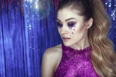 Glam model with artistic make up, glitter tears, wavy ponytail and top made of purple glitter posing against tinsel. Close up portrait of a young beautiful glam Stock Photos