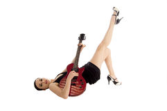 Glam Rock Pinup Girl. Sexy young glam rock pinup girl guitarist in a black mini dress with a red electric guitar Royalty Free Stock Photo