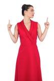 Glamorös modell i den röda klänningen som pekar upp Arkivbild