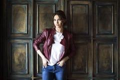 Glamorös ung kvinna i rött läderomslag Royaltyfria Bilder
