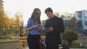 Glamorösa affärspar som pratar och arbetar på den soliga gatan 4K stock video