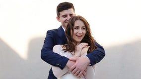 Glamorösa nygifta personer som poserar på bakgrunden av väggen, lager videofilmer