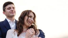 Glamorösa nygifta personer som poserar på bakgrunden av väggen, stock video