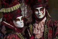 Glamorösa och romantiska par med dräkten och venetian maskering under den venice karnevalet Royaltyfri Foto