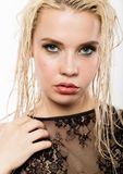 Glamor beautiful blonde girl with wet hair and skin. Bright makeup and plump lips with a damp effect. stock photography