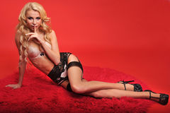 Glamor blond model in lingerie posing sexy in front of red background Stock Photography