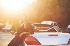 Glamor brunette model in leather jacket posing near convertible car with a sun light. Space for text. Glamor brunette woman in leather jacket posing near royalty free stock image