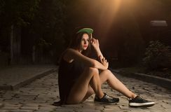 Glamor brunette girl in sport apparel sitting on the cobbles at stock photos