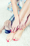 Glamor feet and hands. With red nails and pearls Royalty Free Stock Photo