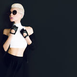 Glamor model on black background in trendy gloves and sunglasses Royalty Free Stock Photos