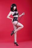 glamor Mulher DJ nos saltos e no traje teatral do látex com fones de ouvido Fotos de Stock