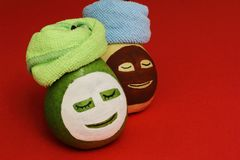Girlfriends in beauty salon. Stylish glamorous ripe juicy pears with yellow and white cosmetic mask and light green and blue towel stock images