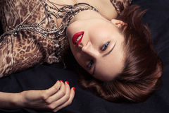 Glamor portrait of beautiful woman lying on black bed Royalty Free Stock Image