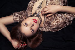 Glamor portrait of beautiful woman lying on black bed Stock Photography