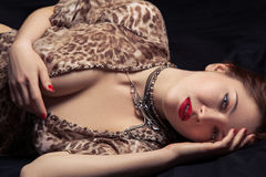 Glamor portrait of beautiful woman lying on black bed Royalty Free Stock Photography