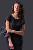 Glamor portrait of a woman in black dress. Glamor portrait of beautiful stylish caucasian young woman model in black dress holding black small handbag Royalty Free Stock Image