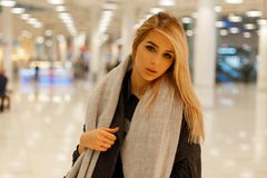 Glamor pretty young stylish beautiful woman blonde with gray eyes with sexy lips in fashionable autumn clothes is resting. In a modern store. Elegant European royalty free stock images