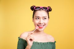 Glamor stylish beautiful young woman model with red lips holding. Candy on yellow background stock images