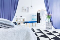 Glamor woman`s bedroom with flowers. On table in entrance to closet with blue stool and curtains Stock Photo