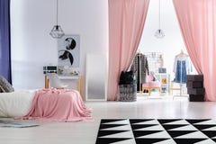 Glamor woman`s bedroom with wardrobe. Glamor woman`s bedroom with pink overlay on bed and pink curtains in entrance to wardrobe Royalty Free Stock Photos