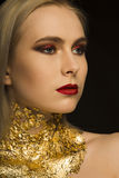 Glamor young model with perfect makeup and gold foil on her neck Stock Image