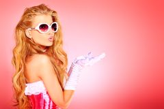 Glamorous. Portrait of a charming blonde woman posing in studio over pink background Stock Photos