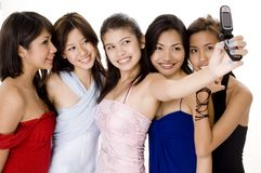 Glamorous #7. Five attractive young asian women in evening wear take their photo using a camera phone Stock Image