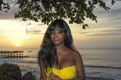 Glamorous African American black woman in chic and elegant summer dress posing relaxed on summer sunset beach Royalty Free Stock Image