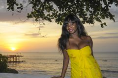 Glamorous African American black woman in chic and elegant summer dress posing relaxed on summer sunset beach Royalty Free Stock Photo