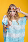 Glamorous beautiful blond woman in sunglasses and blue shirt giving thumbs up on yellow background. happy summer time Stock Photos