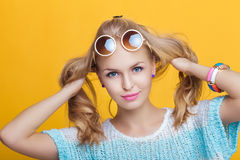 Glamorous beautiful blond woman in sunglasses and blue shirt on yellow background. happy summer time Stock Photos